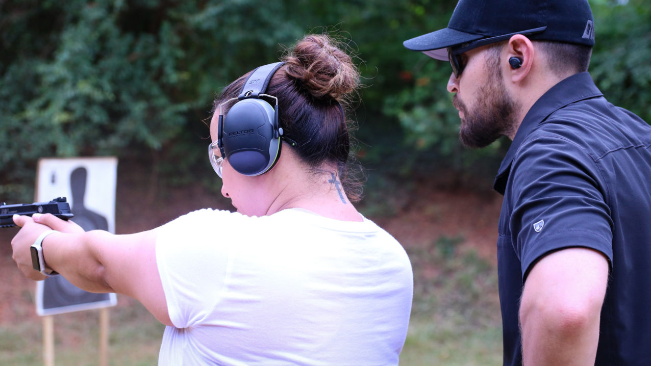 Firearms instructors help female student shoot better
